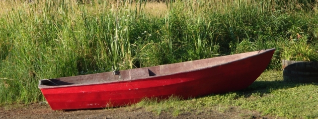red rowboat on maine lake beach